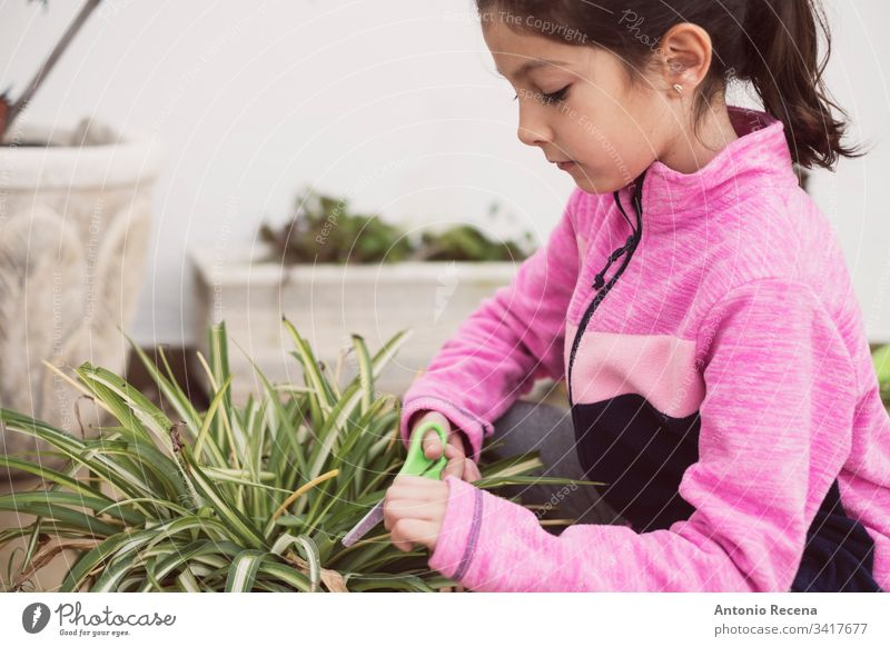girl pruning the pots in her home garden 6-7 years infant alone one person gardeners gardening plants patio spring family real people candid children learning
