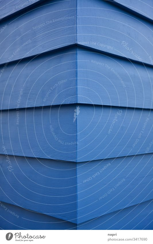Corner of a building whose facade is covered with blue painted wooden planks. Blue Abstract Facade Building Wood Architecture edge lines geometric background
