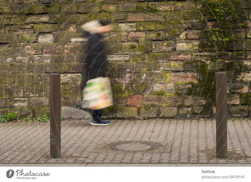 Human or alien with colorful plastic bag walks in front of dirty wall Motion blur Human being Going Wall (building) frowzy Plastic bag variegated Man Pole