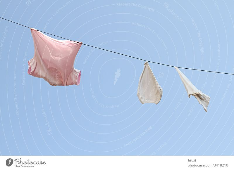 The freshly washed pink t-shirt shows the white underpants to the old washcloth, in front of a blue sky, how to hang wet and fragrant on the rope of the washing line to dry in good weather.