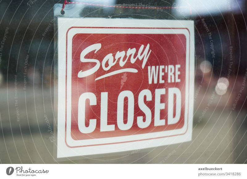 Sorry we're closed sign behind dirty glass door sorry we are closed corona coronavirus business lockdown economy bankruptcy window store shop information