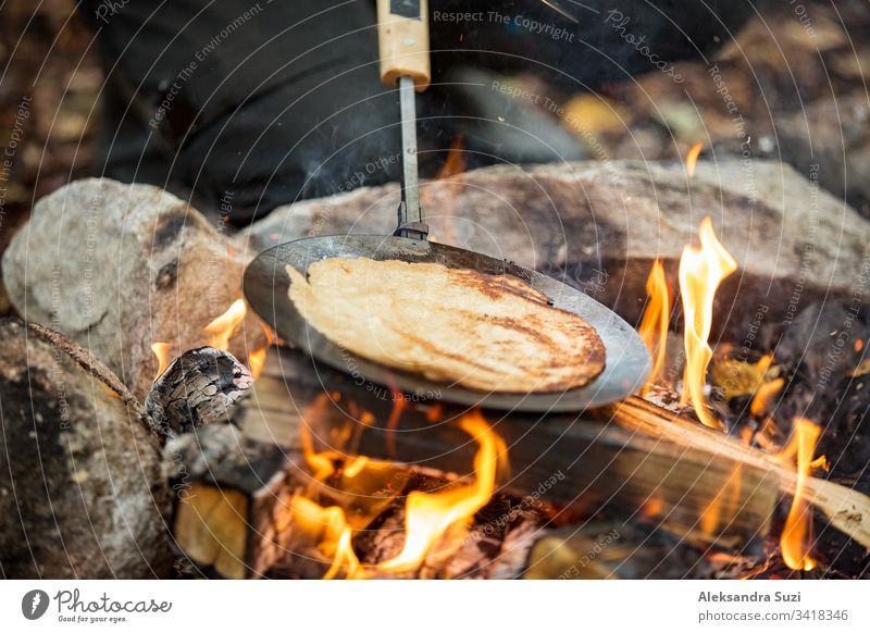 Man and woman making pancakes on campfire in forest on shore of lake, making a fire, grilling. Happy couple exploring Finland. Scandinavian landscape. active