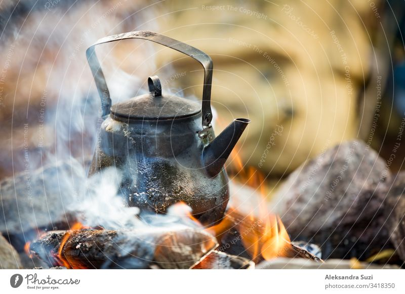 Man and woman making coffee in big kettle on campfire in forest on shore of lake, making a fire, grilling. Happy couple exploring Finland. Scandinavian landscape.