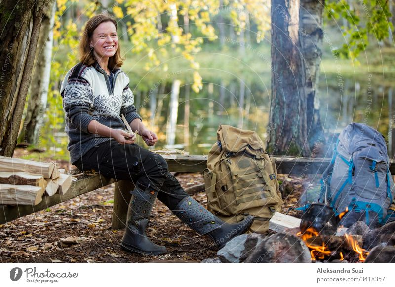 Man and woman roasting on campfire in forest on shore of lake, making a fire, grilling. Happy couple exploring Finland. Scandinavian landscape. active adventure