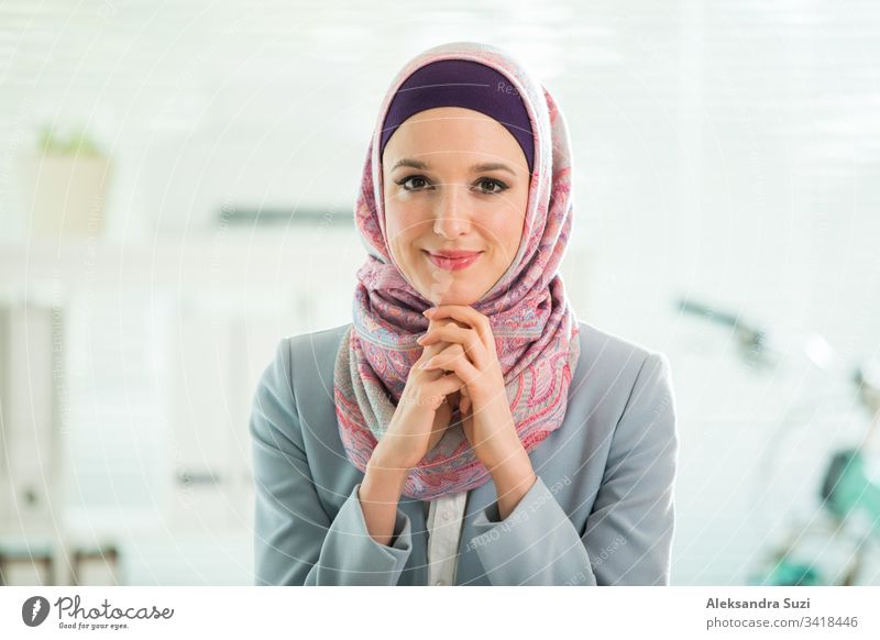 Beautiful stylish woman in hijab and eyeglasses, sitting at desk with laptop in office. Portrait of confident muslim businesswoman. Modern office with big window, bicycle on background.