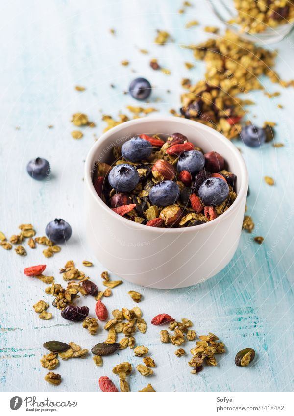 Matcha green tea granola with berries homemade matcha bowl pastel turquoise background oats goji dried fruit seeds sesame nuts healthy plant based vegan