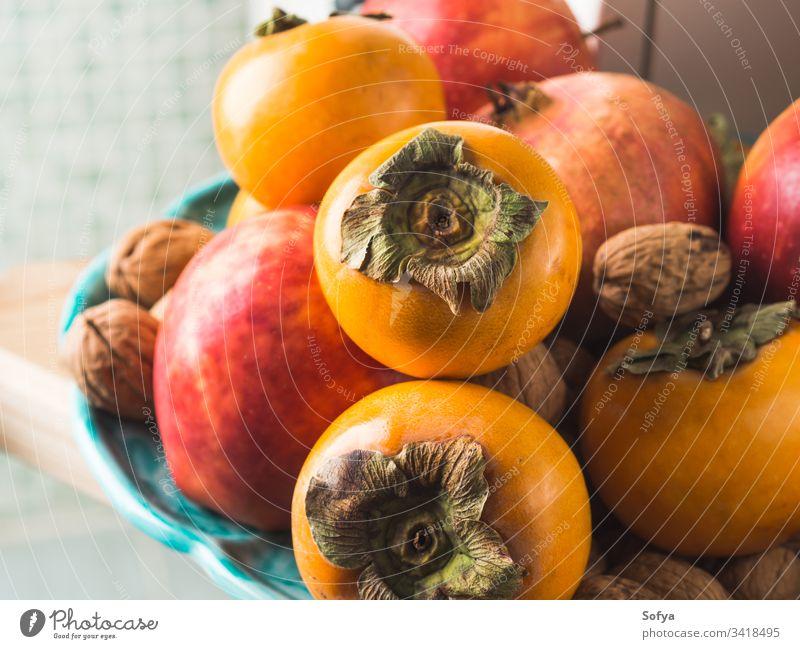 Autumn fresh fruit food in the kitchen autumn fall persimmon background vegan vegetarian pomegranate apple harvest healthy organic eat seasonal winter orange