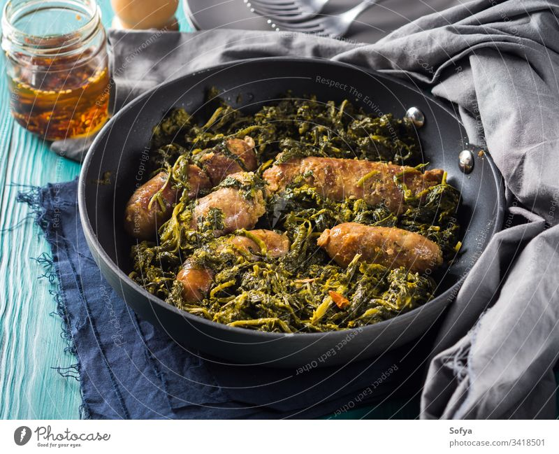 Italian sausages with rapini broccoli in a skillet meat italian kale black second dish dinner lunch meal serve table wooden set green traditional neapolitan