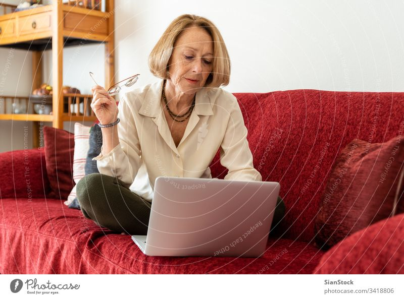 Elegant mature woman using computer at home elderly lady aged beauty wellbeing carefree comfort attractive comfortable casual blond relaxed middle-aged leisure