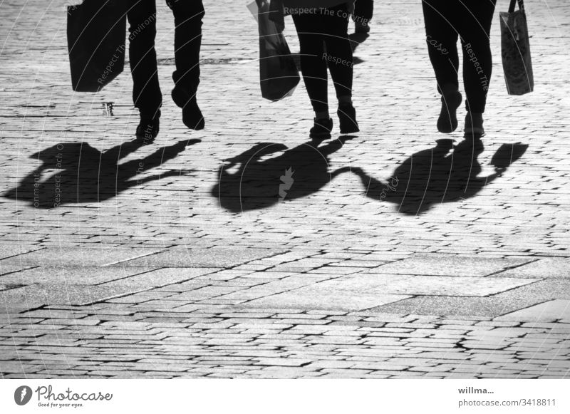 Shadow of a group of people - the lively threesome Group Legs Shopping shopping bag city stroll Shopping trip couple 3 Walking triple feet Human being Street