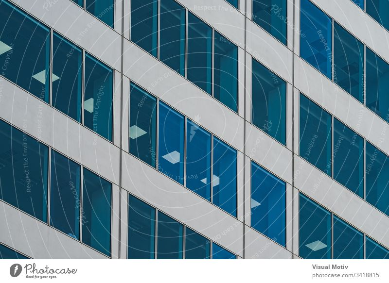 Symmetrical blue windows of an office building made of aluminum and glass facade architecture architectural architectonic urban color structure geometric