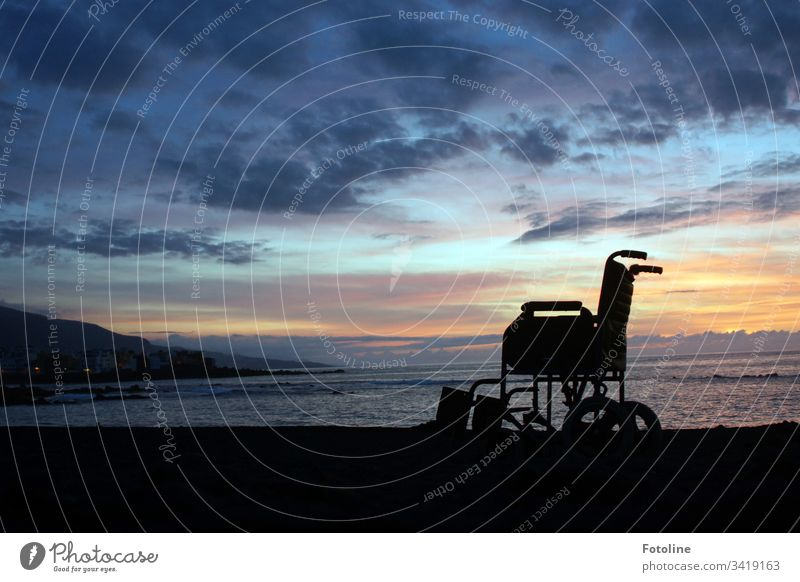 Wheelchair on the beach of Puerto de la Cruz in Tenerife at sunset Mountain Landscape Exterior shot Sky Nature Colour photo Deserted Clouds Sunset