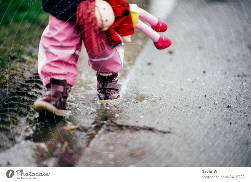 girl child runs with doll through puddle along a street Girl Street Puddle Wet Dangerous car traffic Walking Insecure Child Toddler peril Bad weather Autumn