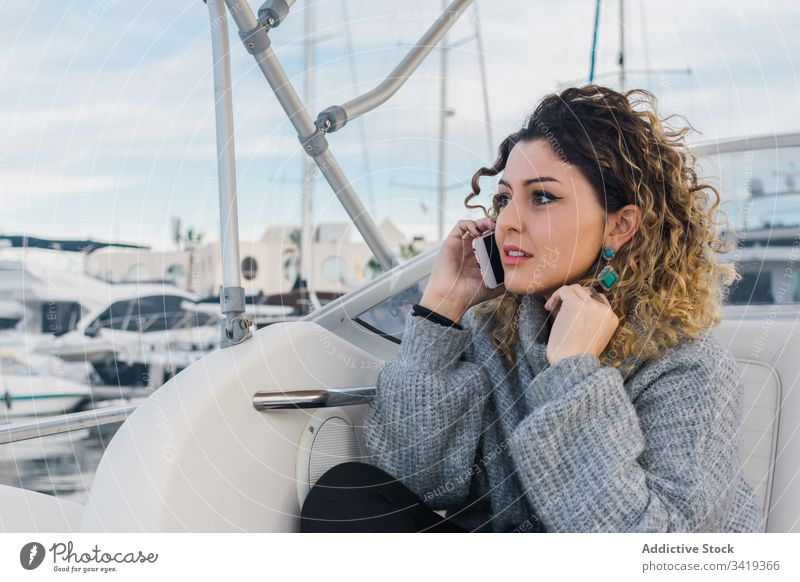 Content lady with smartphone in yacht woman using smile female browsing mobile phone laugh satisfied content enjoy surfing watch connection device gadget
