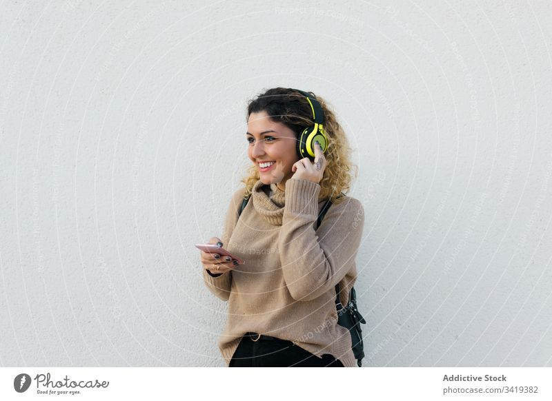 Content woman with headphones and smartphone using smile casual female laugh enjoy content listen music device gadget modern communicate connection lifestyle