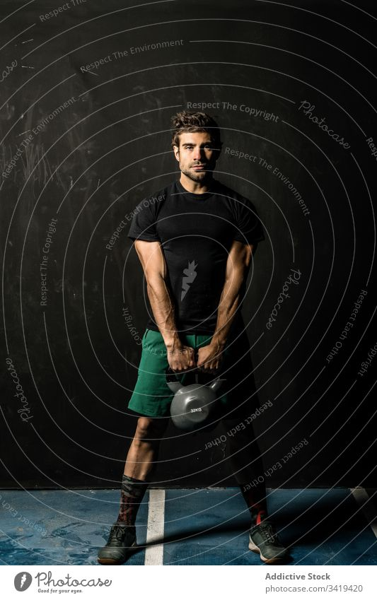 Muscular sportsman with kettlebell in gym weightlifting functional training muscular fitness healthy male athlete exercise power strong body sportswear physical