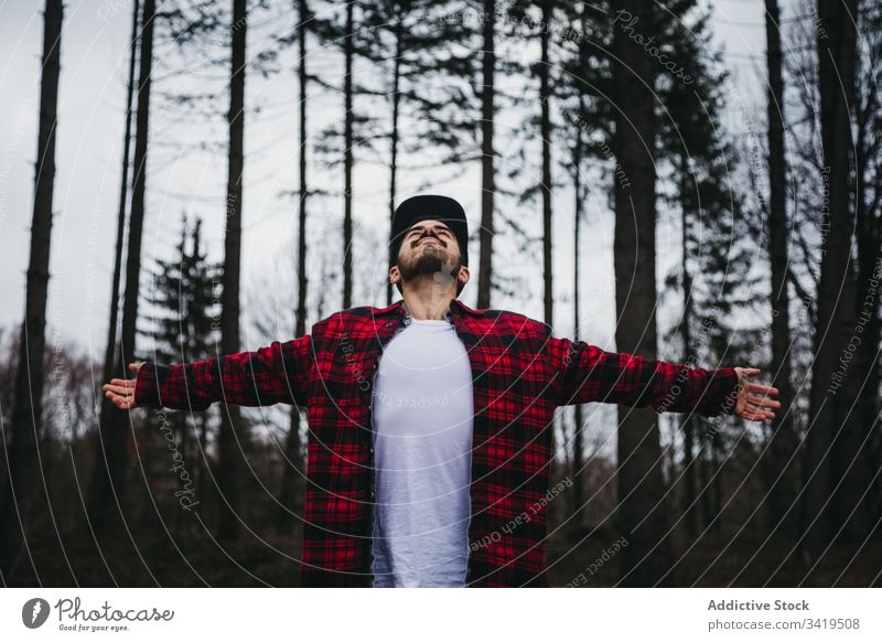 Excited guy enjoying fresh air of beautiful woods man forest nature tree relax freedom male casual spread arms cloudy overcast travel young happy hipster