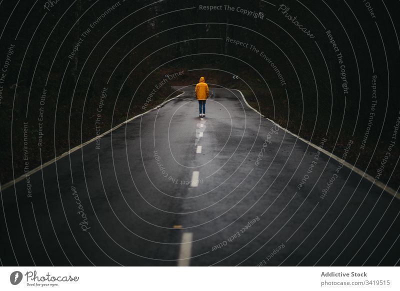 Unrecognizable man walking on lonely road in autumn forest nature rain way tree season weather empty casual yellow coat jacket freedom countryside asphalt scary