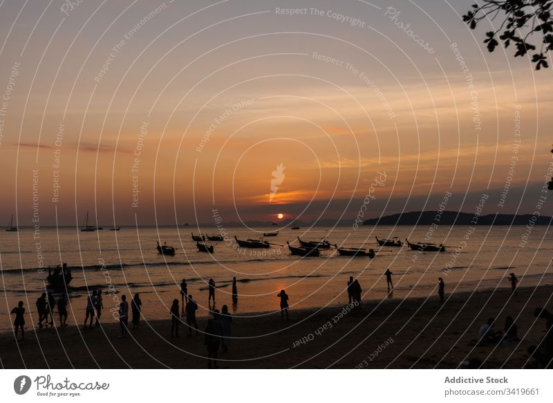 People on shore of ocean in evening sunset beach sea boat nature water travel vacation sky coast wave tropical paradise dusk vessel beautiful transport