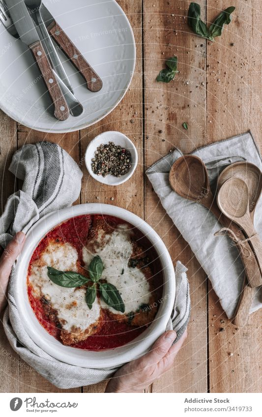 Unrecognizable person putting bowl full of chicken with cheese and basil in tomato sauce on table dish utensil roast food delicious tasty parmesan meal cuisine