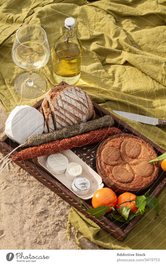 Pastry and tangerines with cheese and sausages near wine during picnic food blanket beach pie bread delicious tasty fresh meal snack gourmet drink beverage