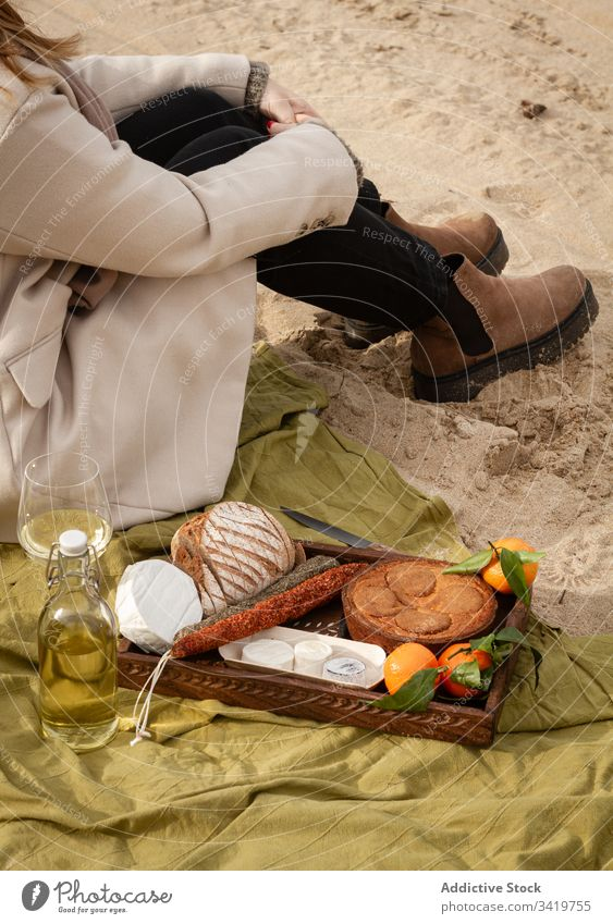 Crop woman sitting near wine and tray with pastry and tangerines with sausages and cheese picnic beach food blanket rest sand female bread pie drink beverage