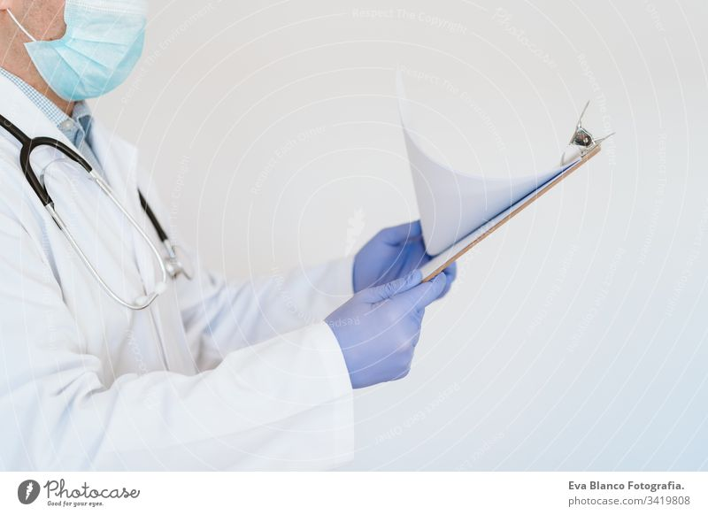 unrecognizable doctor wearing protective mask and gloves indoors. Holding a folder. Corona virus concept man professional corona virus hospital working