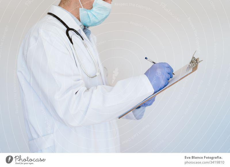 unrecognizable doctor wearing protective mask and gloves indoors. writing notes on a folder. Corona virus concept man professional corona virus hospital working