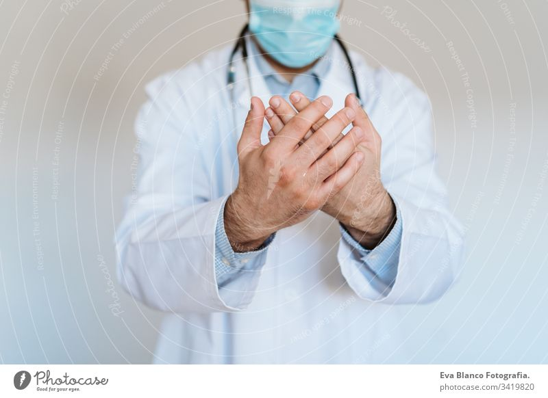 caucasian doctor wearing protective mask and gloves indoors. Using an alcohol gel or antibacterial disinfectant. Hygiene and corona virus concept man