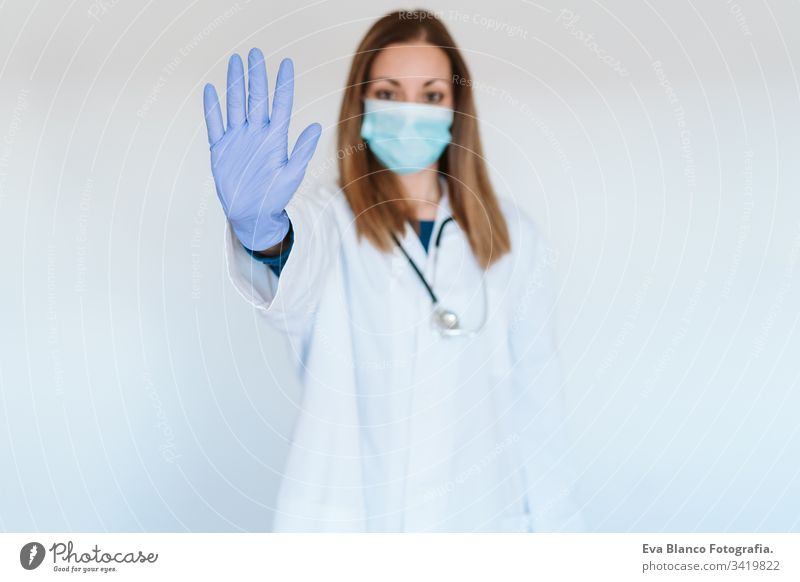 portrait of doctor woman wearing protective mask and gloves indoors. Making a stop sign with hand. Corona virus concept professional corona virus hospital