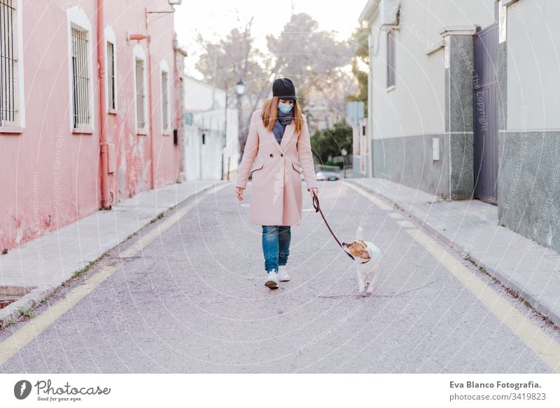 caucasian woman in the street wearing protective mask and walking with her dog. corona virus concept outdoors mobile phone technology internet public adult