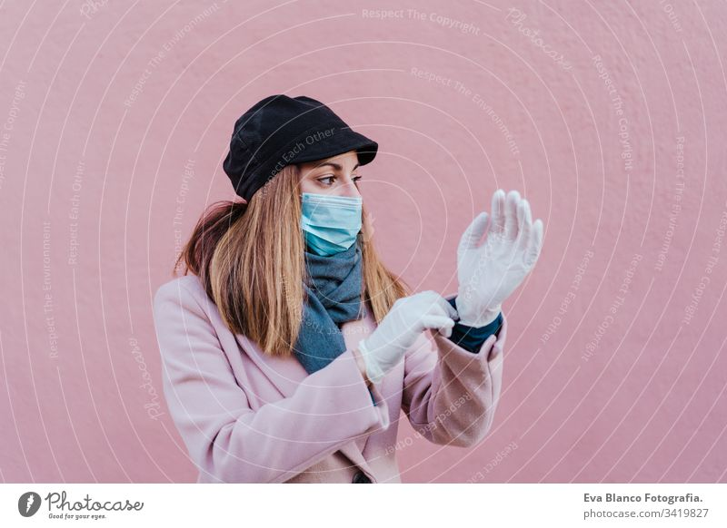 caucasian woman in the street wearing protective gloves and using mobile phone. corona virus concept mask outdoors technology internet public adult infection