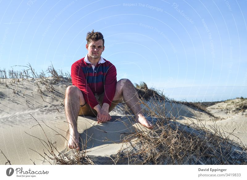 Guy in a red and blue rugby shirt sitting on sand dunes Beach Beach dune Sand Vacation & Travel Coast Dune Ocean Relaxation