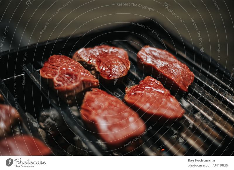 raw meat on a barbecue grill barbecuing barbeque bbq beef blood cooking dinner food grid grilled grilling heat hot meal nutrition outdoors party portion
