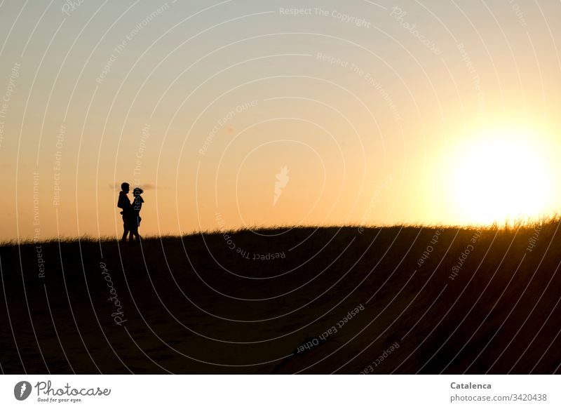 The sun sets on the horizon, on the left the silhouette of an embracing couple Sunset Couple Twilight Evening Clouds Sky Dusk Nature Landscape Exterior shot