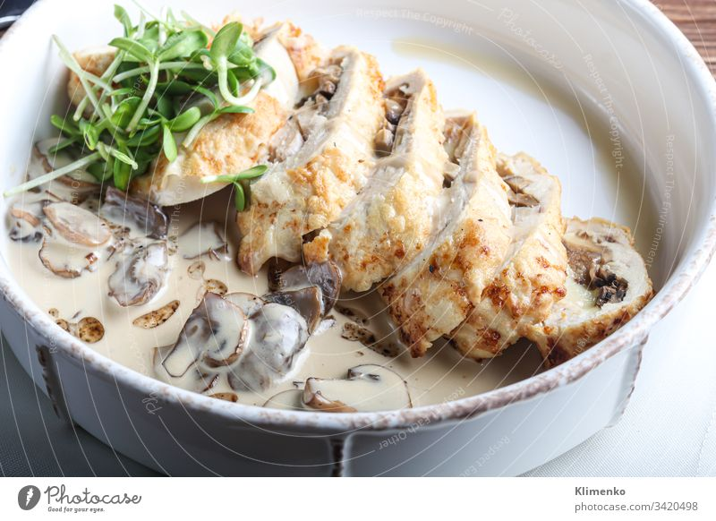 Chicken breast roll with mushrooms. Next to the champignon sauce. On a dark background. Decorated with microgreen. food meat easter dinner meal plate pork