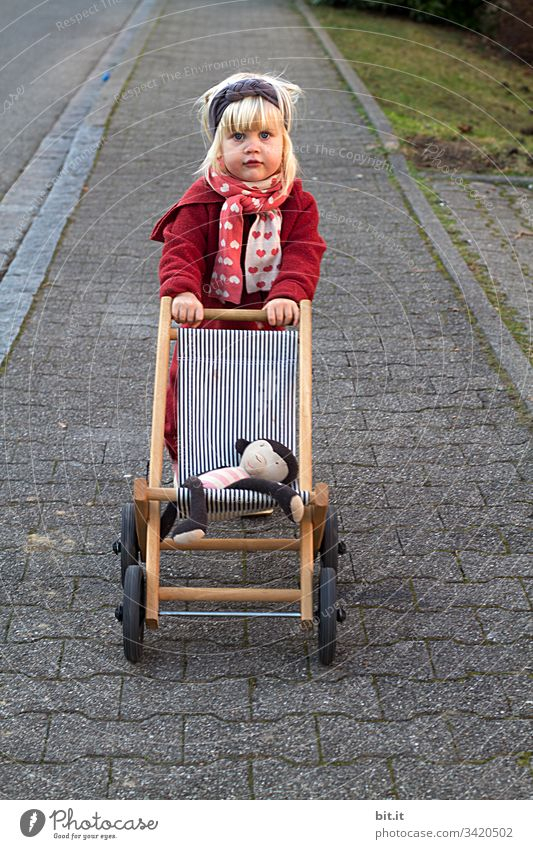 The monkey lies comfortably, the girl is happy and pushes the doll's carriage over the sidewalk. Infancy doll car To go for a walk off Push Playing luck Cute