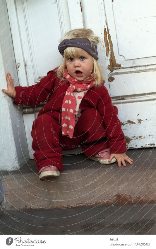 Small, blond, talking girl in winter clothes, climbs a staircase, in front of an old, white wooden front door. Child Toddler Playing Joy Infancy Cute 1