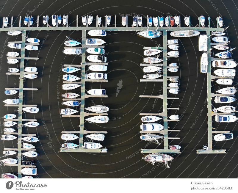 Aerial view of many boats docked in a marina, against dark water, created by dji camera. Marina sailing decks aerial view coastal seaside leisure nautical
