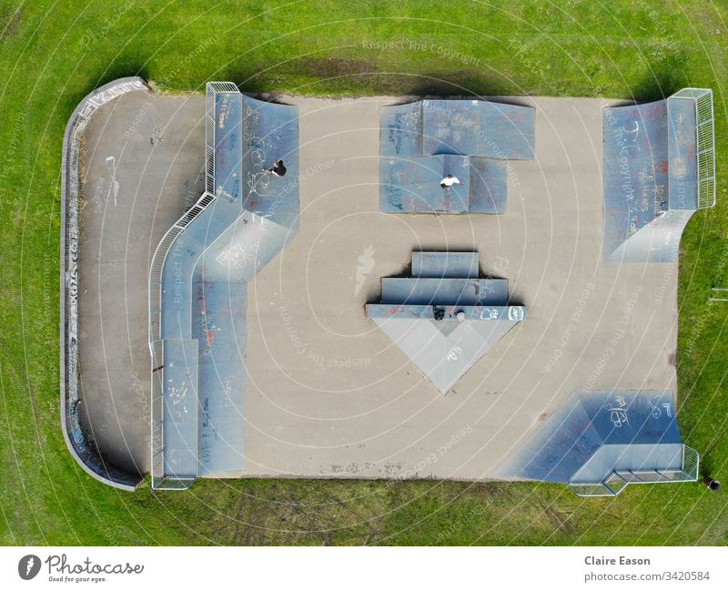 Aerial view  of a skatepark with 2 unidentifiable teens. Grey-blue ramps against a grass background.  created by dji camera Skatepark skateboarding scooters