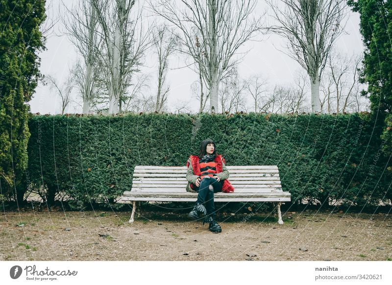 Young woman relaxing in a green park in winter outdoor solitude alone loneliness nature natural cold youth fresh real candid rest resting calm tranquiltiy