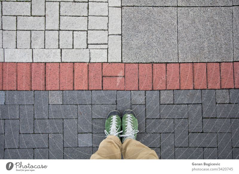 Top view of a man standing on the colorful geometrical pavement street outdoor foot travel floor stone ground shoe person sidewalk lifestyle urban city road pov
