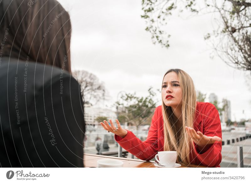 Two angry friends discussing while sitting at coffee shop. two discussion talking woman friendship complicated negative problems girls speaking worried argument