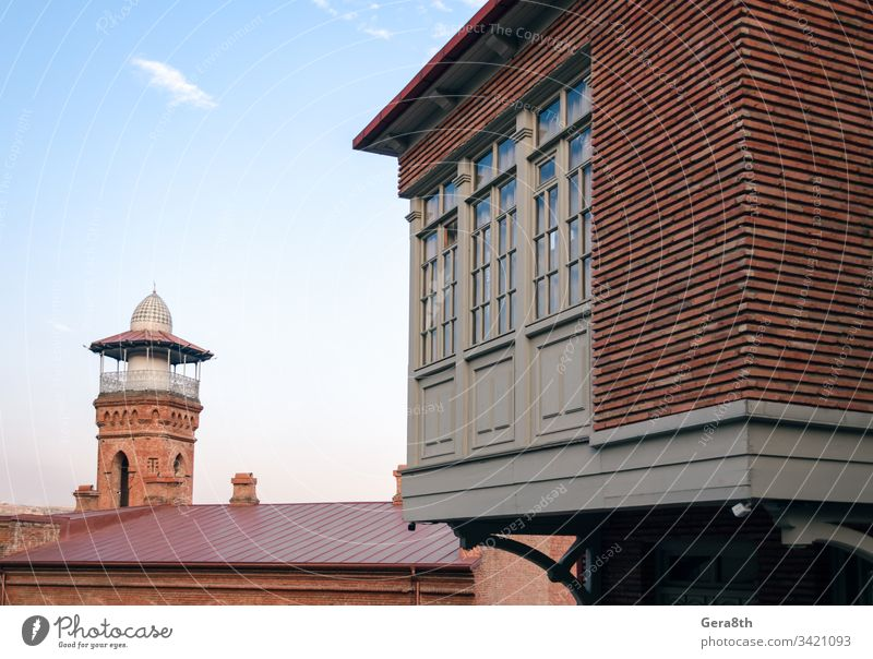 tall old tower and modern building with windows in Georgia Caucasus architecture blue brick city clouds color corner day dome house religion retro roof sky