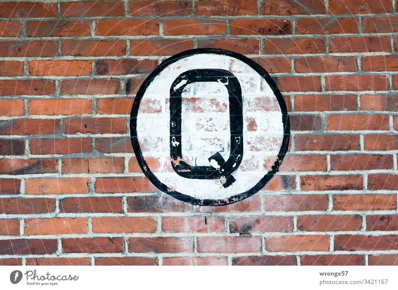 Large black Q on white background on a brick wall q Letters (alphabet) Colour photo Day Characters Exterior shot Capital letter sign Brick wall Building
