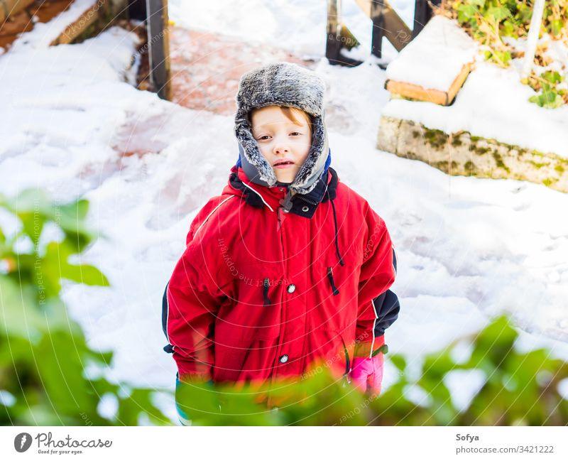 Little blonde boy in winter outerwear outdoors child snowsuit happy little look face eyes white caucasian kid cold hat cap cute fun season playing clothing