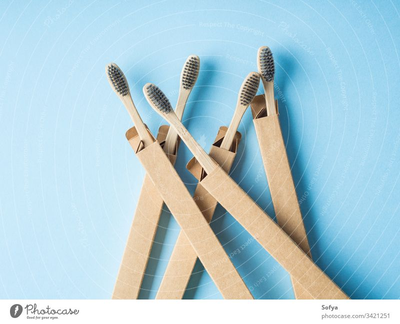 Bamboo biodegradable toothbrushes on blue bamboo dental ecofriendly cardboard packaging box zero waste background hygiene health minimal abstract care clean