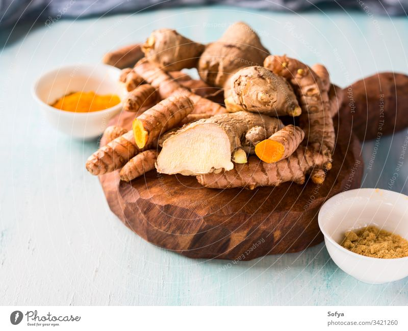 Turmeric and ginger in powder and roots on board turmeric spice healthy aroma background closeup blue exotic dry flavor food fresh golden indian ingredient