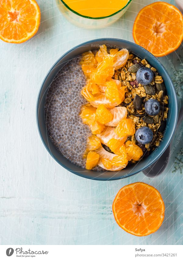 Chia pudding with tangerines and granola chia pudding bowl pastel turquoise matcha tea wooden background blueberry breakfast chia seeds dessert food plant based