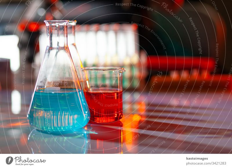 Illuminated laboratory flask filed with colorful chemical solutions with shadows on the table. Laboratory, science, reaserch, chemistry... consept. glassware